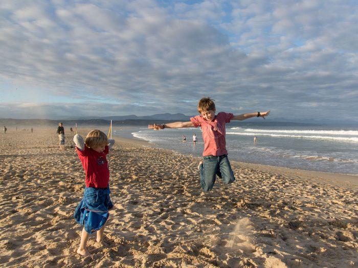 Kinder am Strand springen in die Luft